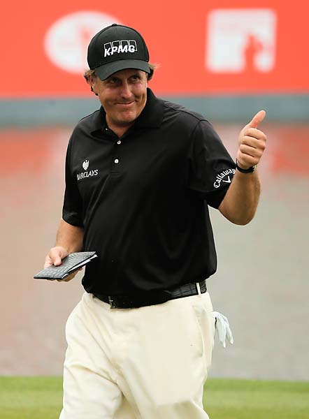 Phil Mickelson walks off the green on the 18th hole Sunday. Mickelson went low Sunday, shooting 65 and finishing 14th.