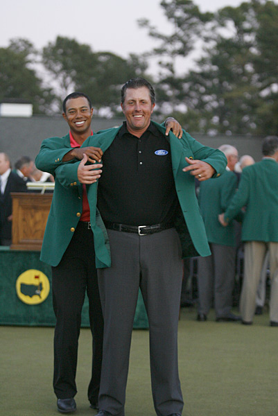 Longtime rival Woods presented Mickelson with the green jacket.