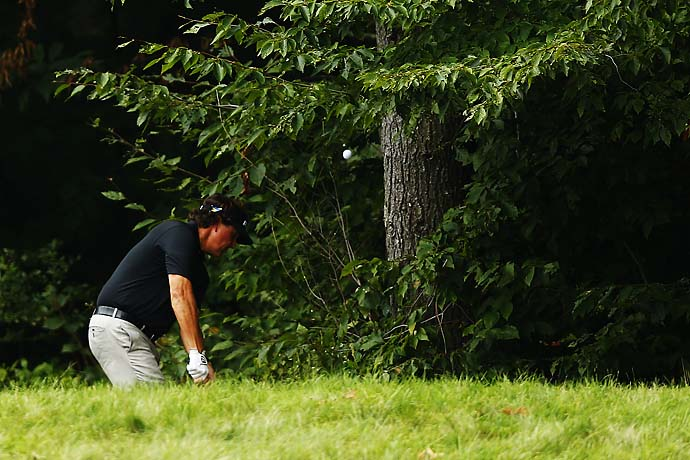 Phil Mickelson plays from out of the trees on nine. Even playing partner Tiger Woods was impressed with how often Mickelson got up and down from a tough spot on Saturday.