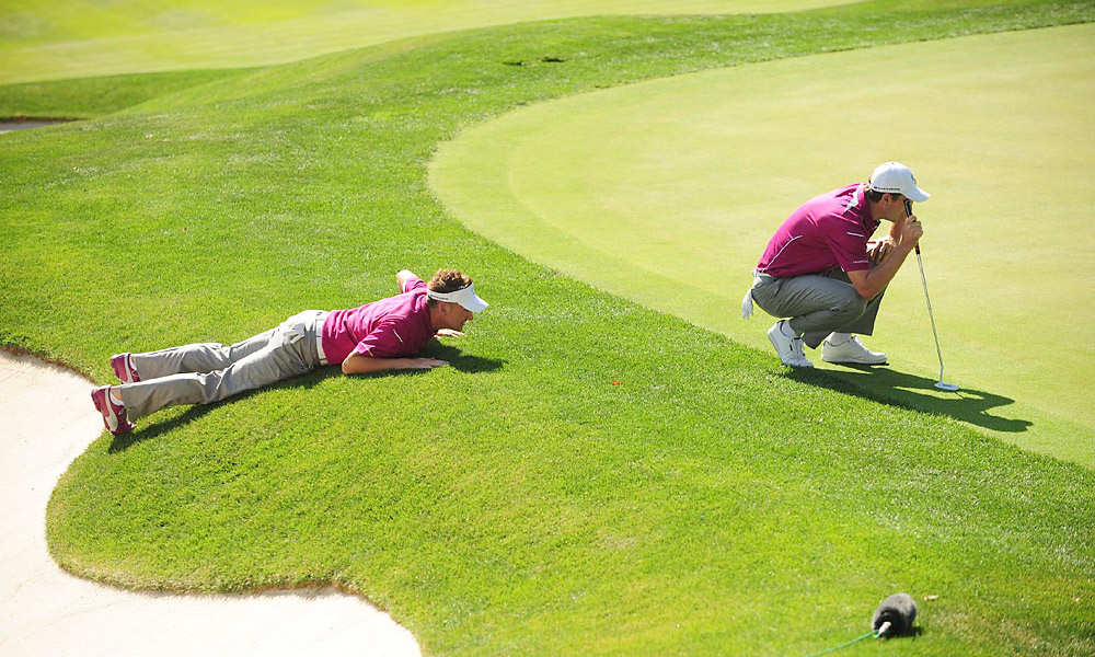 Poulter and Rose read a putt during their foursomes match.