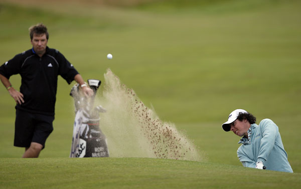Rory McIlroy chipping out of a bunker in front of the 14th hole.