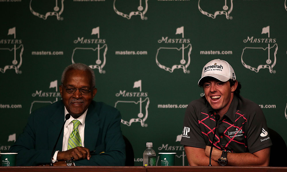 Augusta National Golf Club member Ronald Townsend sits with Rory McIlroy after McIlroy's cell phone rang during the press conference.