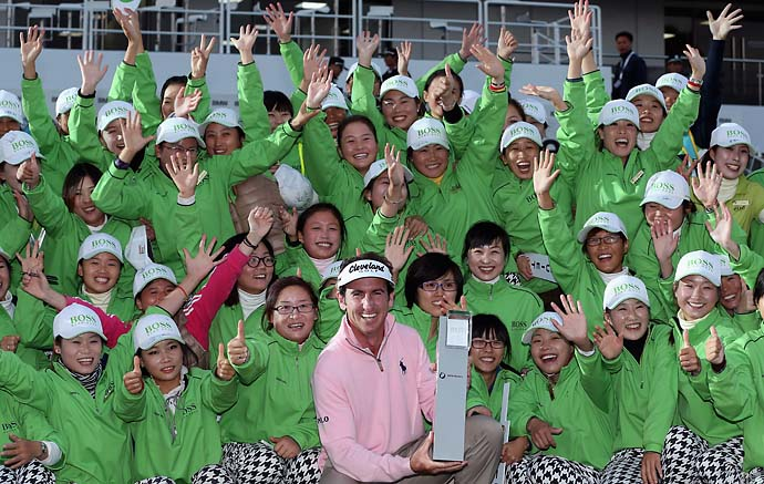 Gonzalo Fernandez-Castano poses with the trophy amidst a group of volunteers after wining the BMW Masters at Lake Malaren Golf Club on Oct. 27, 2013 in Shanghai.