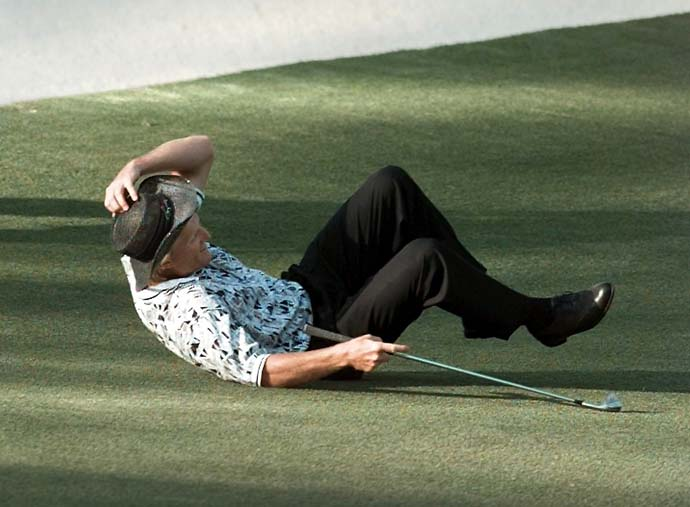 Greg Norman falls to the ground after missing his shot for an eagle on the 15th hole during final round play of the 1996 Masters.