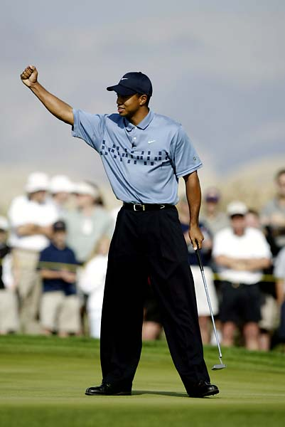 Tiger Woods pumps his fist after making a birdie putt on the fifth green to win a skin worth $25,000 during the Skins Game on November 30, 2002, at the Landmark Country Club in Indio, California.