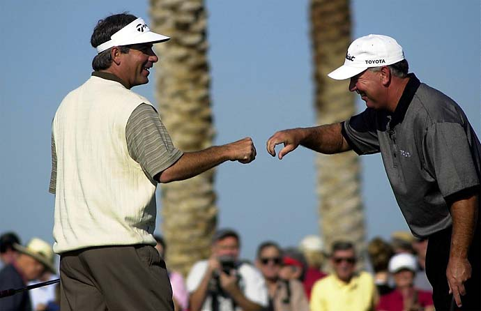 Fred Couples is congratulated by Mark O'Meara after Couples won a skin, for $50,000, on the 11th hole Sunday, Dec. 1, 2002, during the Skins Game at the Landmark Golf Club in Indio, Calif.