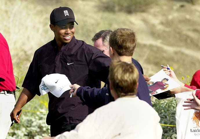 Tiger Woods signs autographs for fans during the Skins Game pro-am at the Landmark Golf Club in Indio, Calif., Friday, Nov. 29, 2002.