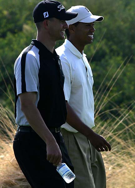 Adam Scott talks with Tiger Woods as they walk down the fairway during day 1 of the Merrill Lynch Skins Game at Trilogy Golf Club on Nov. 27, 2004, in La Quinta, Calif.