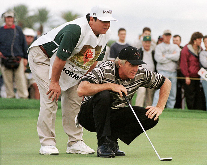 Greg Norman lines up a putt on the fourth green, with the aid of his caddy Tony Navarro, November 29 at the 1998 Skins Game at Rancho La Quinta Country Club in Indian Wells, Calif. Norman was shut out of the money in the first day of the event, but did birdie the fifth hole.