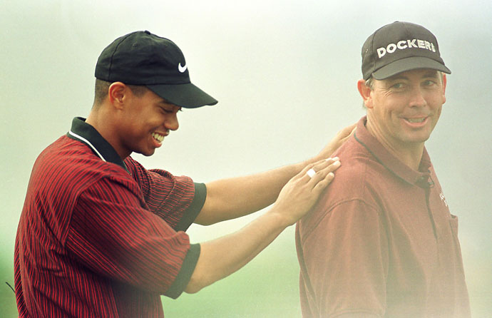 Tiger Woods congratulates Tom Lehman after he made the putt to save the hole on the 18th during the second round of The 1987 Skins Game at Rancho La Quinta Country Club in La Quinta, California. The hole was replayed and Mark O'Meara won the hole. Lehman won a total of 10 skins for $300,000 for the tournament.