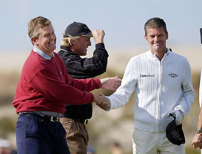 Greg Norman tips his hat after winning his second skin worth $200,000 as Colin Montgomerie shakes hands with Jesper Parnevik during the second day of the Skins Game, Sunday, Nov. 25, 2001, in Indio, Calif. Norman won two skins for the tournament totaling $1 million.