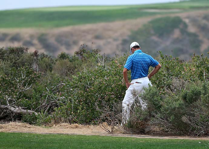 Gary Woodland looks at hs lie after hitting his tee shot in the brush on the 17th hole during the final round of the Farmers Insurance Open on Sunday. Woodland made double bogey on the hole, ending his chance to win.