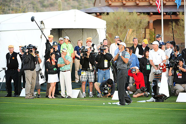 Woods took several swings with crowds of media watching.