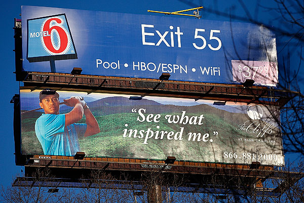 A billboard for Tiger Woods's new golf community the Cliffs is seen below a billboard for Motel 6 in Asheville, N.C.
