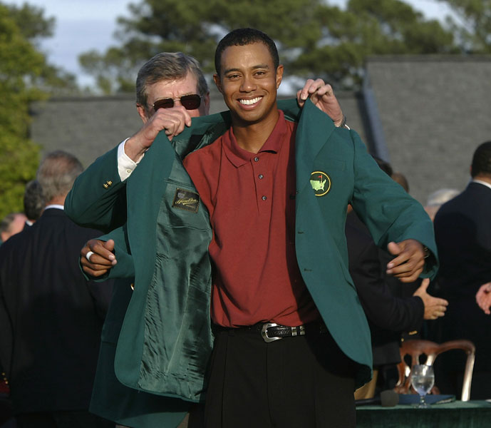 """Since Woods won as the defending champion, Augusta National chairman William """"Hootie"""" Johnson had the honor of helping Woods into his green jacket."""