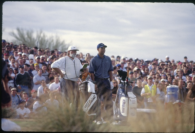 Woods and caddie Fluff Cowan wait on the tee. (Cowan now caddies for Jim Furyk.)