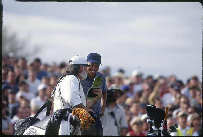 """Woods and Cowan study the yardage on 16. (Tiger still has that headcover style; he calls it """"Frank."""")"""