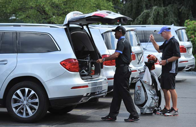 Tiger Woods and caddie Joe LaCava unpack the clubs from Tiger's courtesy car at the Oak Hill Country Club parking lot. Tiger already had his golf shoes on when he arrived.