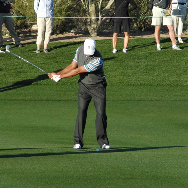 Here's where Tiger's coil starts. The source of his power is this wide, sweeping takeaway where he turns his upper body against the resistance of his legs. No early set of the wrists here — Tiger lets the weight of the club do the hinging.