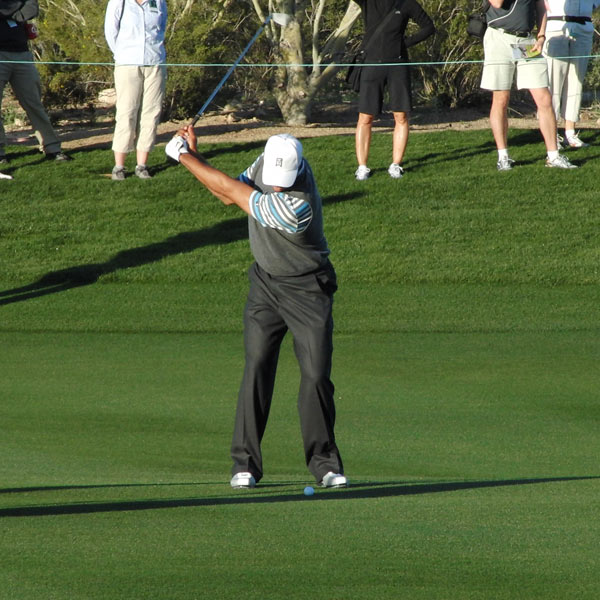 Here Tiger approaches the top, the last moment before he engages his weight onto his rebuilt knee. His shoulders, arms and hands finish the backswing as a unit, keeping his swing compact and in control.