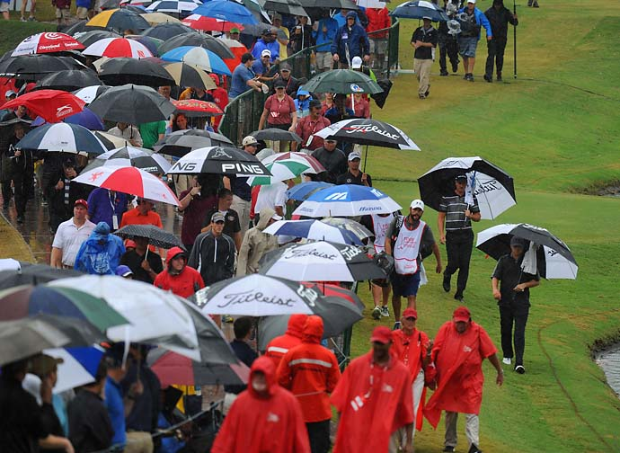 Players and fans walk to the 18th green during the third round of the Tour Championship on a rainy Saturday when an umbrella was the most popular accessory for fans and players.