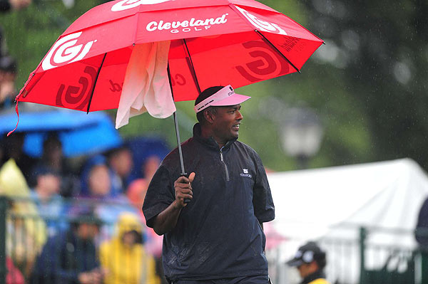 Vijay Singh tried to stay dry before teeing off on the first hole, which he parred.