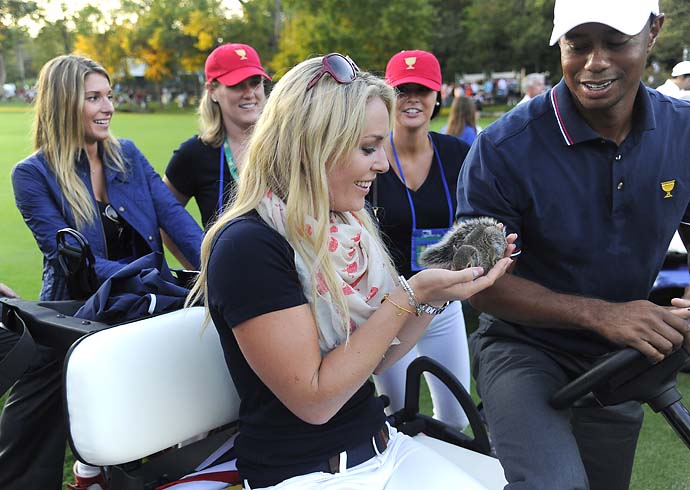 Lindsey Vonn holds Sammy the Squirrel as Tiger Woods of the U.S. Team looks on during the Day One fourball matches.