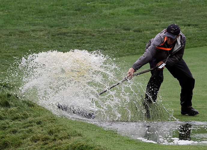 A member of the maintenance crew attempts to clear water from one of the holes.