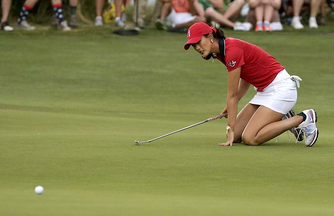 Michelle Wie falls down after missing a birdie putt on the 18th hole of her singles match against Caroline Hedwall on Sunday. Hedwall won the match, which clinched the Solheim Cup for Team Europe.