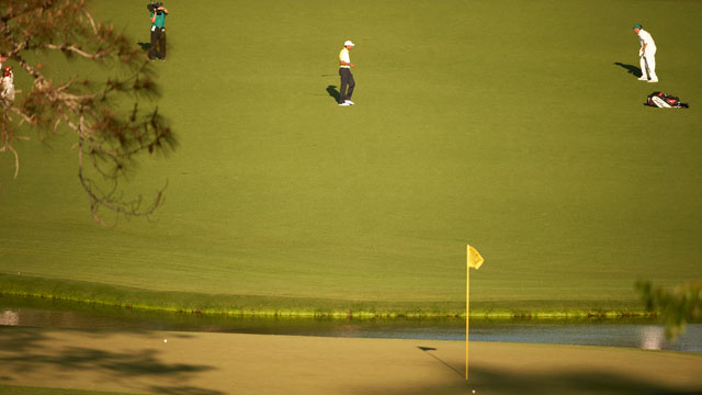 Tiger Woods reacts after his third shot hit the pin and rolled into the water.