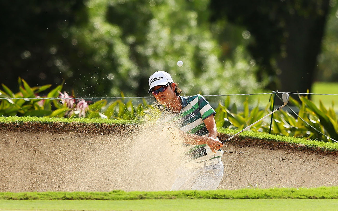 Kevin Na blasts from a bunker on the third hole.