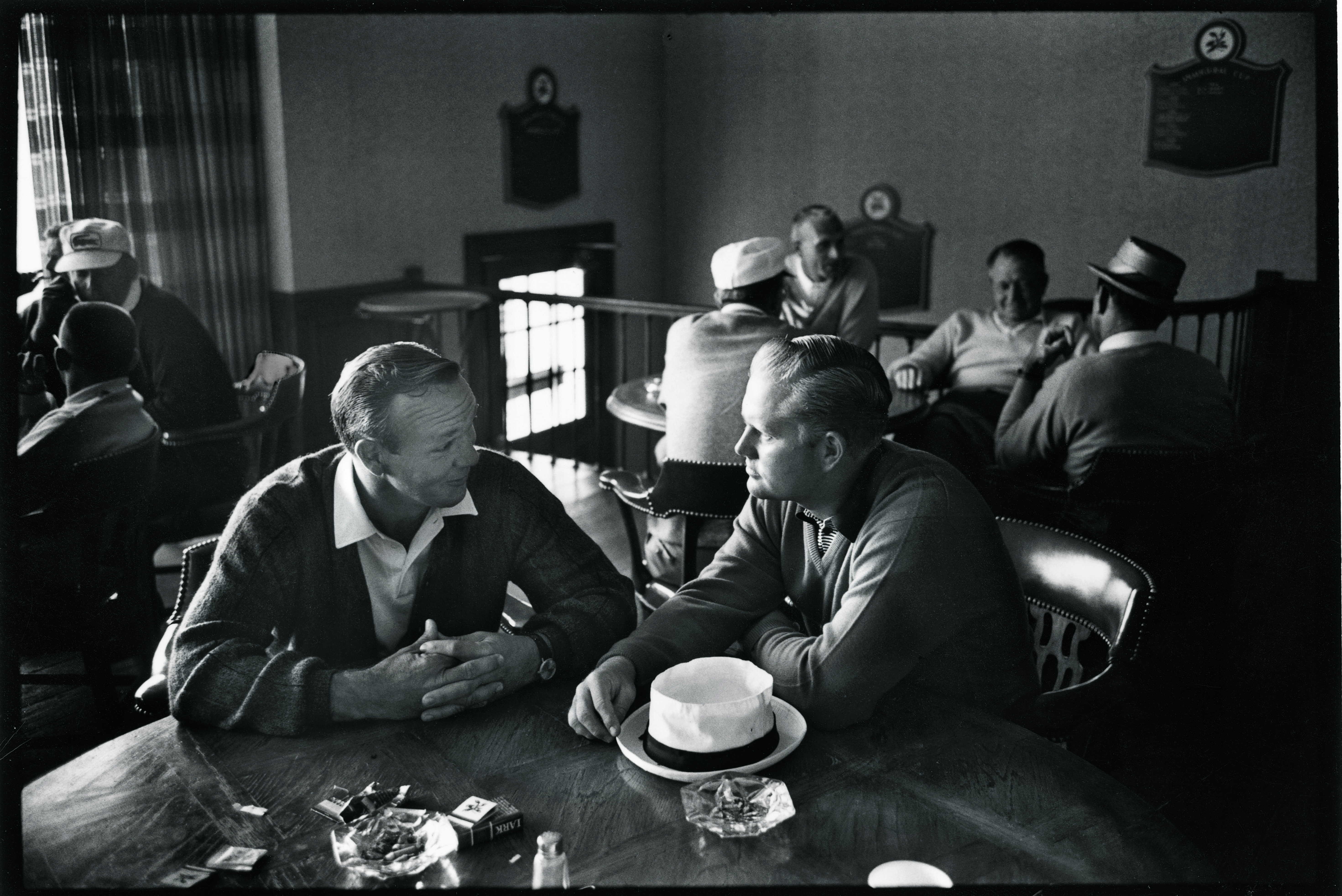 Arnold Palmer and Jack Nicklaus sitting at a table at Laurel Valley Country Club during the 1965 PGA Championship in Ligonier, Pa