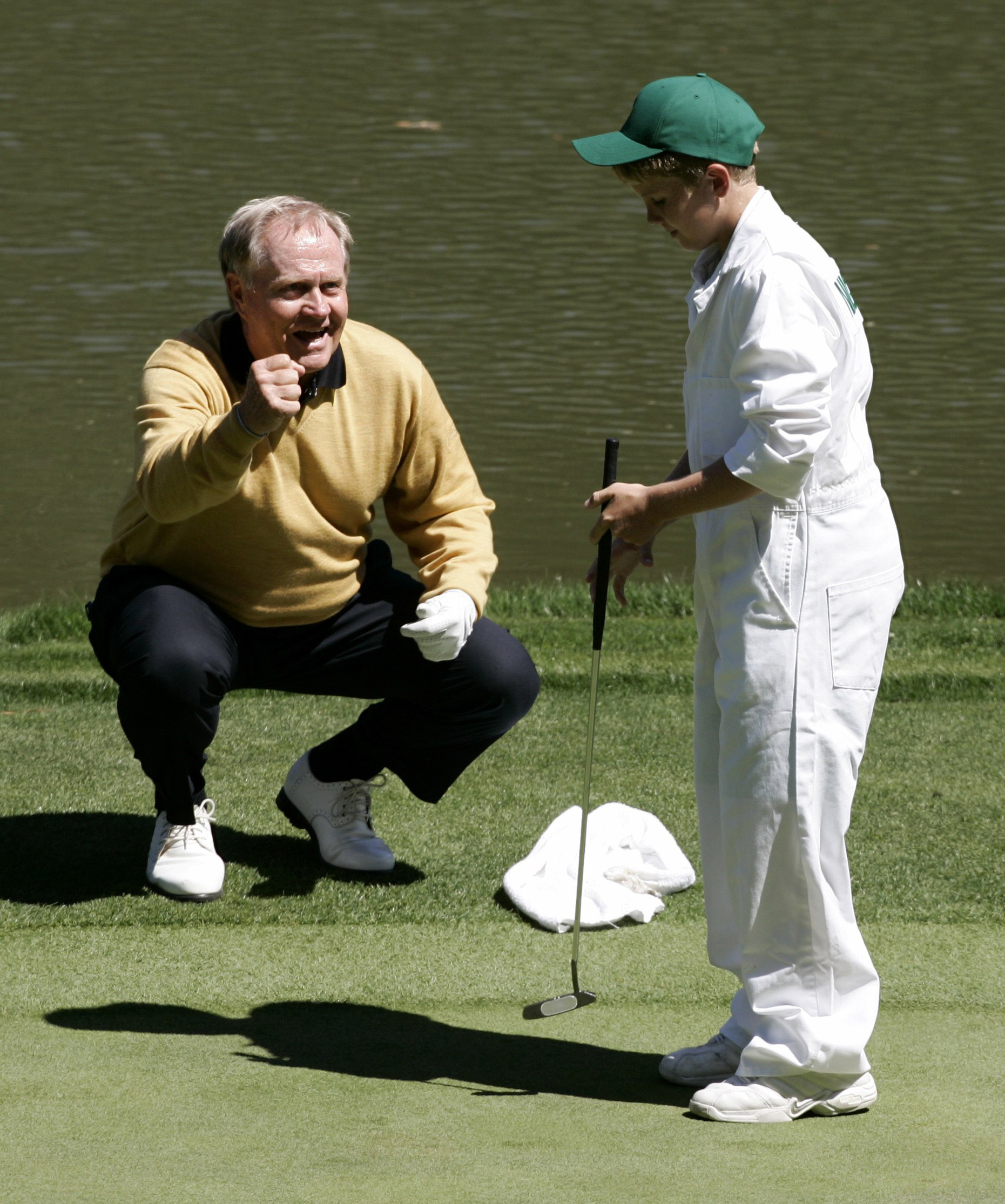 Jack Nicklaus celebrates as his grandson and caddie, Charlie Nicklaus, 11, makes a putt on the final hole of the annual par three tournament at the Augusta National Golf Club in Augusta, Georgia, April 5, 2006.