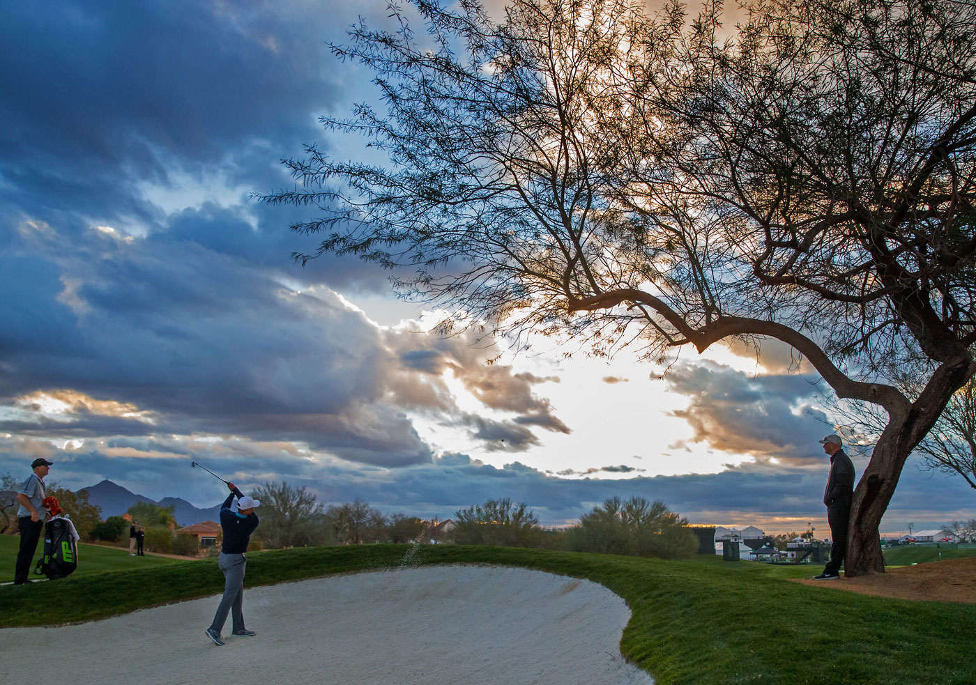 Tiger Woods blasts from a bunker during his practice round at TPC Scottsdale.