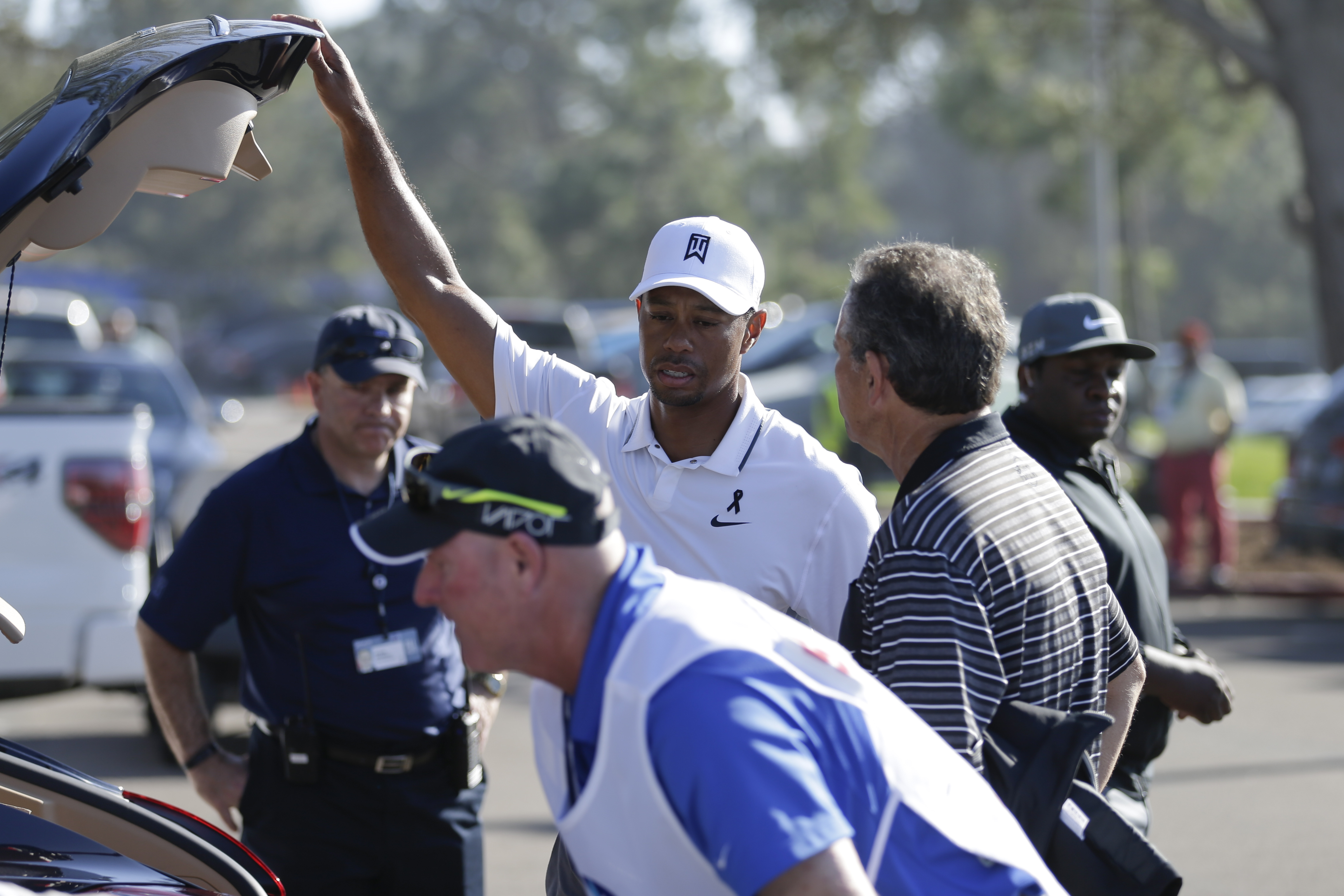 Tiger Woods loads his car after withdrawing in the first round of the Farmers Insurance Open.