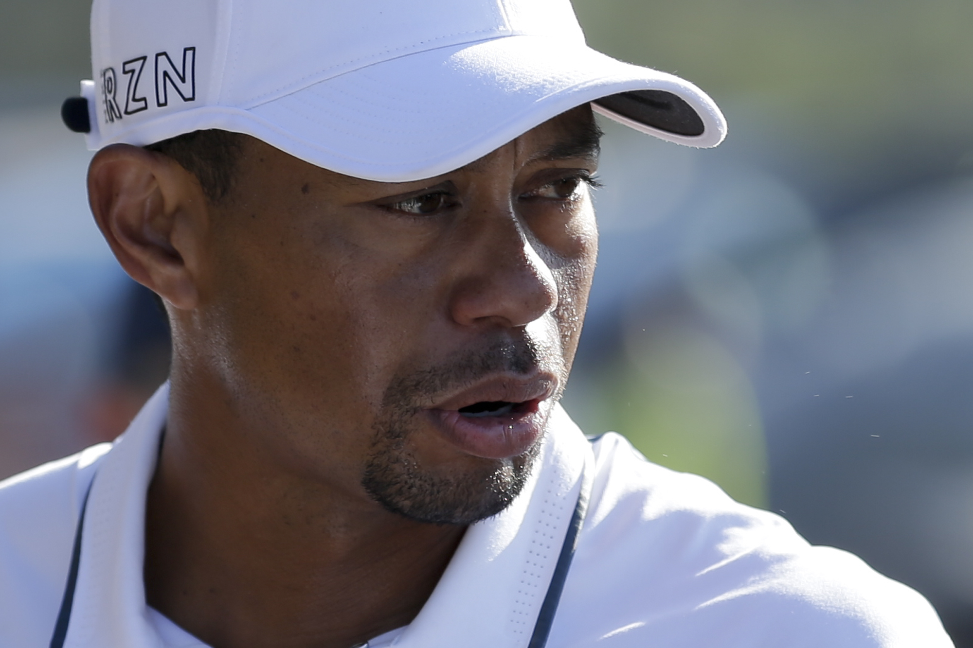 Tiger Woods looks back while loading his car after withdrawing in the first round of the Farmers Insurance Open golf tournament Thursday, Feb. 5, 2015, in San Diego. (AP Photo/Gregory