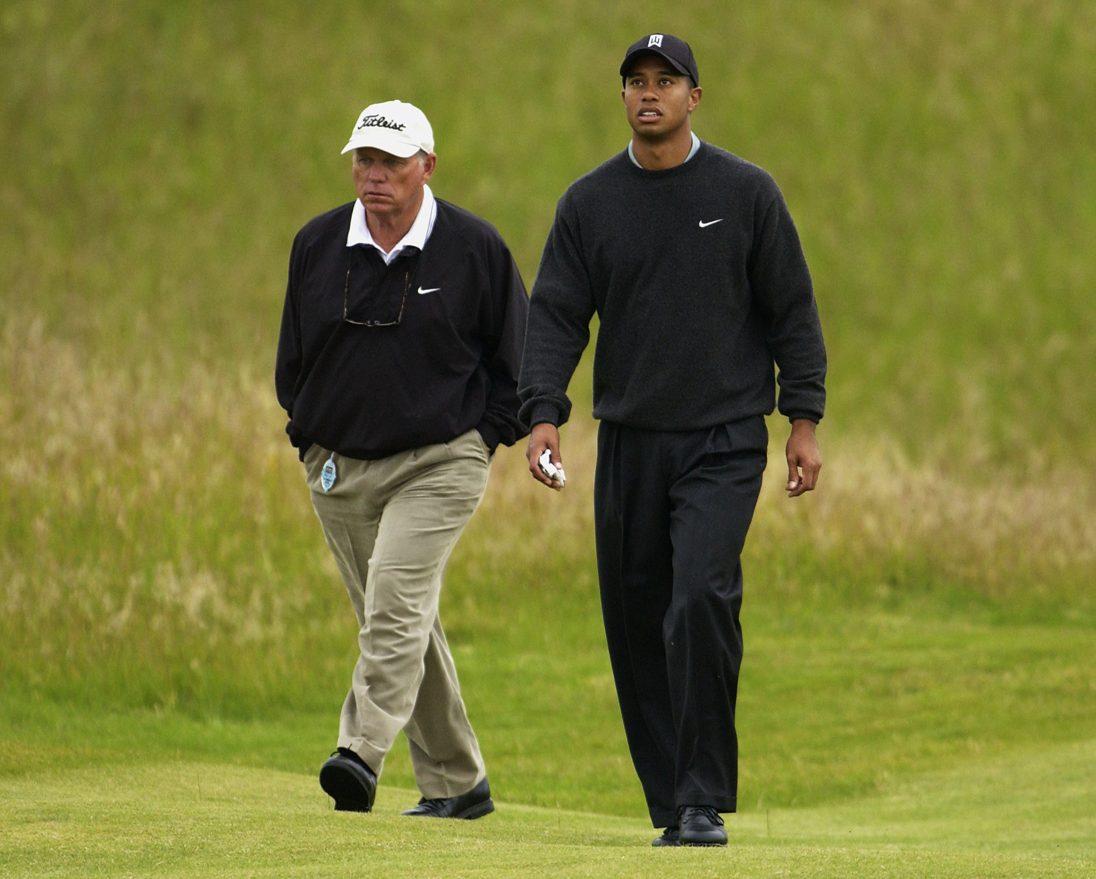 Tiger Woods and Butch Harmon walk the sixth fairway during a practice round for the 131st Open Championships at Muirfield Golf Club in Gullane, Scotland, on July 16, 2002.