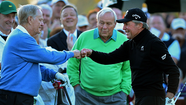 Jack Nicklaus reaches out to fist bump Gary Player following Player's drive from the first tee at the 2014 Masters.