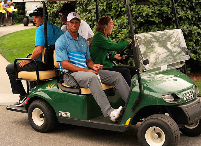 Woods is carted toward the practice area by a visibly excited volunteer.