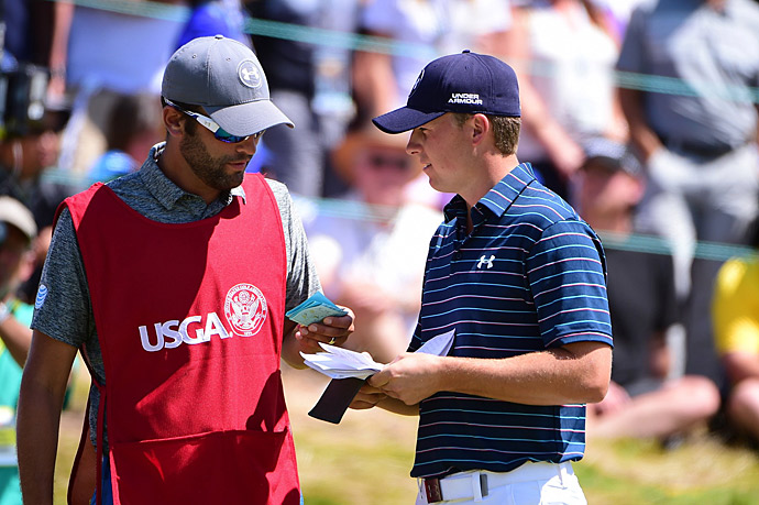 Spieth chats with his caddie Michael Greller before starting the final round.