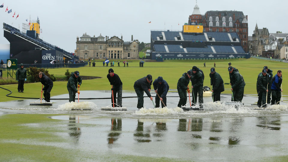 Workers clear the course of water after heavy rainfall prior to the second round of the 144th Open Championship.