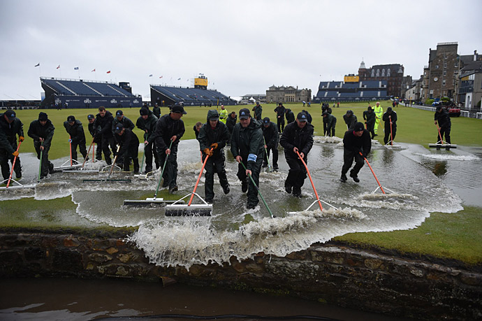 The flooding created a bizarre scene at the Old Course, with the maintenance crew using squeegees to push the water into the Swilcan Burn.