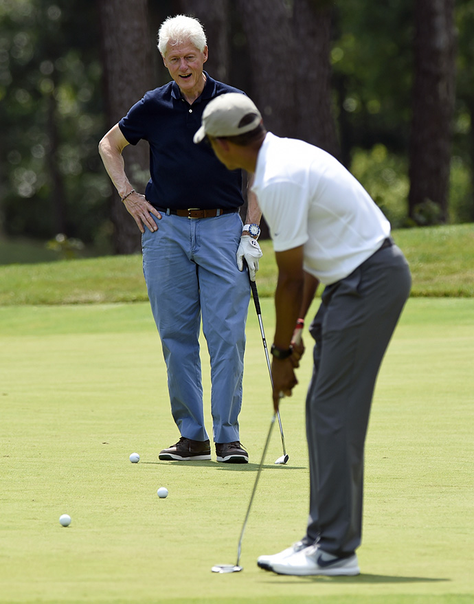 President Barack Obama watches his putt as he plays golf with former President Bill Clinton on the first hole at Farm Neck Golf Club in Oak Bluffs, Mass., on Martha's Vineyard, Saturday, Aug. 15, 2015.