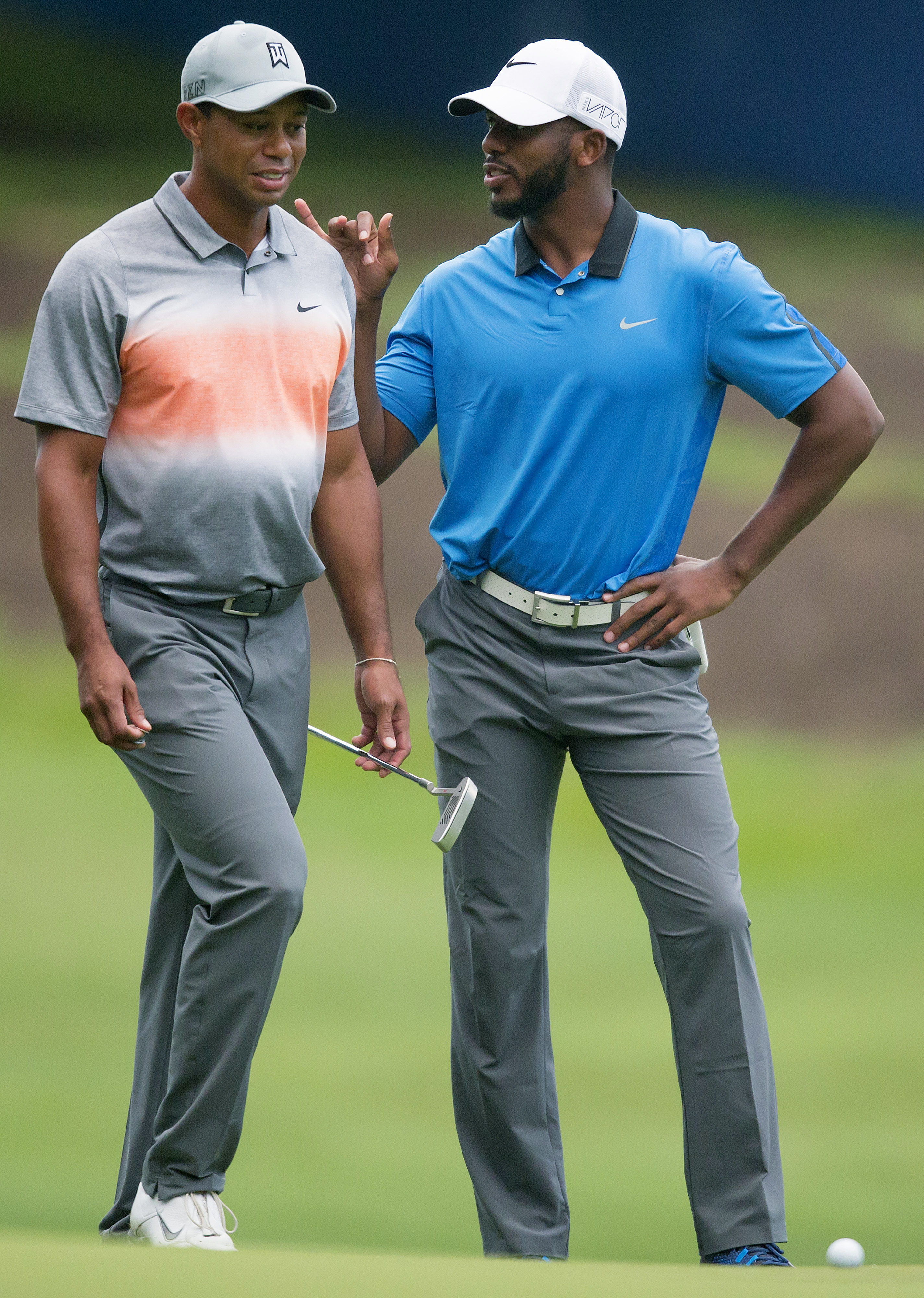 Tiger Woods chats with Los Angeles Clippers basketball player Chris Paul during the pro-am at the Wyndham Championship on Wednesday, Aug. 19, 2015, at Sedgefield Country Club in Greensboro, N.C.