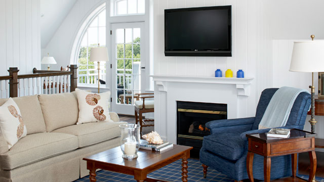 The living room features traditional, coastal New England-style furnishings.