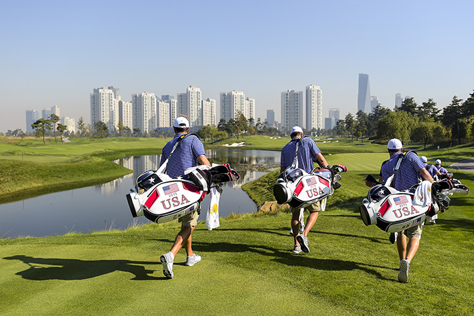 Team USA caddies carry bags as they walk off the third hole tee box during practice for The Presidents Cup at Jack Nicklaus Golf Club Korea.