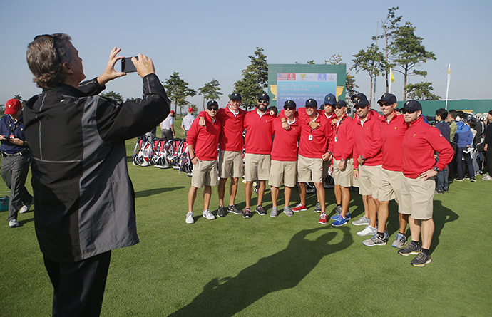 Peter Jacobsen snaps a photo of the caddies of the United States team on the practice ground.