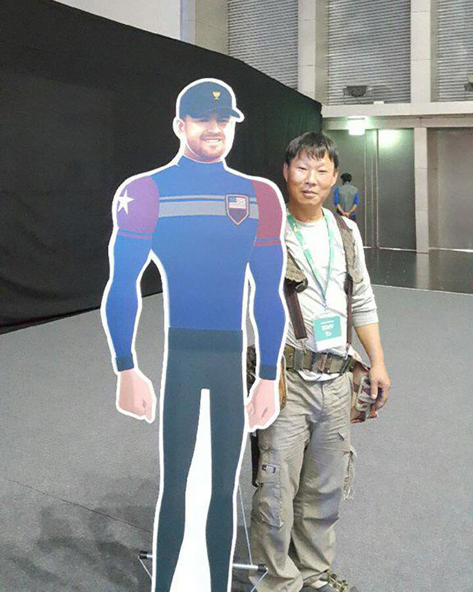 Despite being a late addition, J.B. Holmes' avatar was made in time. A fan poses with a cardboard cutout of it.