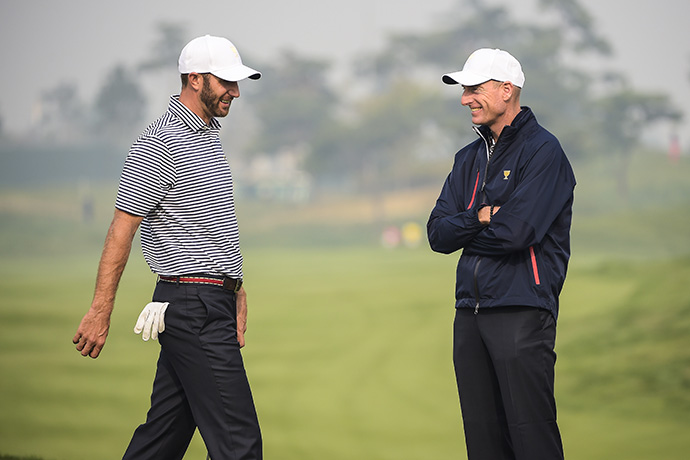 Dustin Johnson speaks with Captain's Assistant Jim Furyk on the second hole during practice for The Presidents Cup.