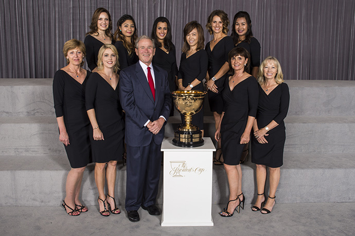 The wives and girlfriends of the International Team pose with Former President George W. Bush.